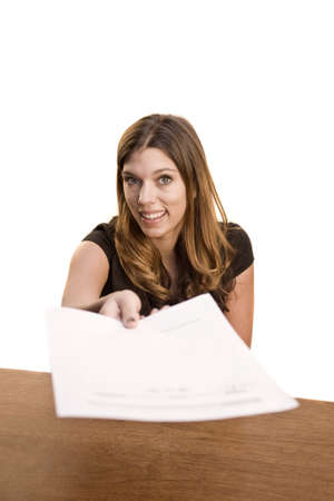 Woman at desk handing over piece of paper Stock Photo