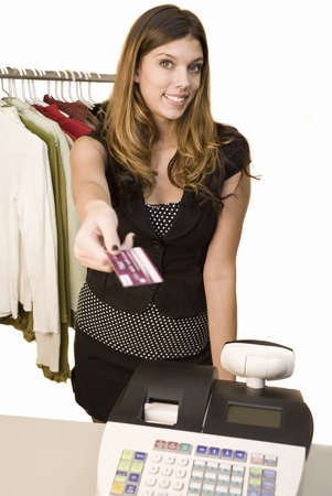 paying: A young woman at a register with credit card