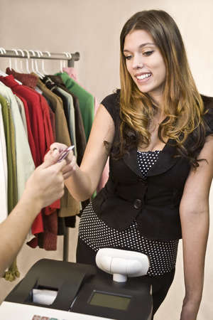 A young woman at the register with credit card photo