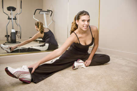 A young woman stretching on the floor in a gym photo