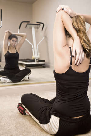 A young woman stretching in front of a gym mirror photo