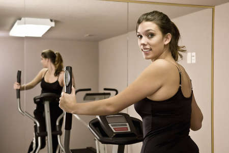 Young woman on treadmill working out in gym photo