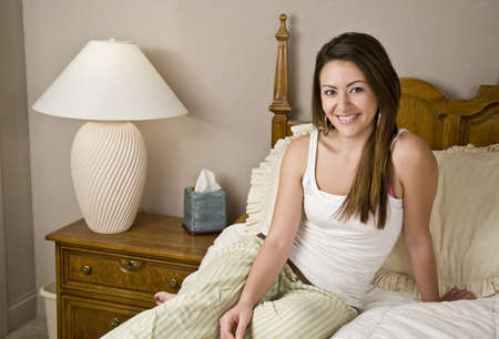 A young woman sitting on bed smiling photo