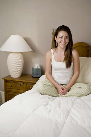 Woman sitting in bed relaxing and smiling photo