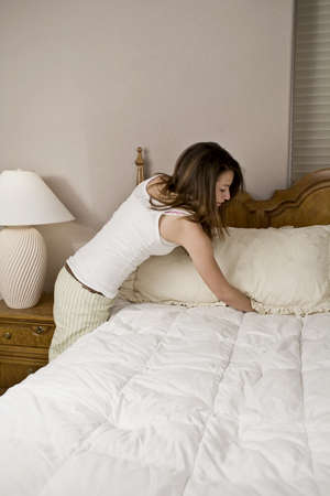 Young woman making bed and organizing room Stock Photo - 4088467