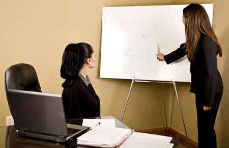 financials: Two young professional business women going over financials Stock Photo