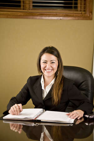 A pretty professional business woman working at her desk Stock Photo - 4088471