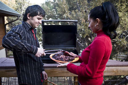 A couple having a barbeque on the patio at home photo