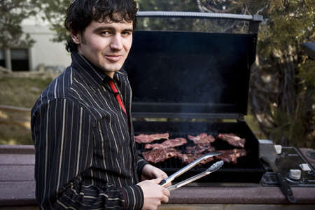 A handsome man grilling steak on the barbeque 版權商用圖片 - 4170338