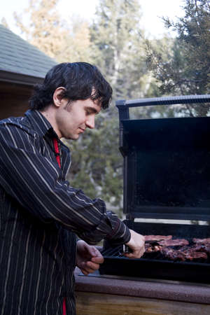 A handsome man grilling meat on the barbeque photo