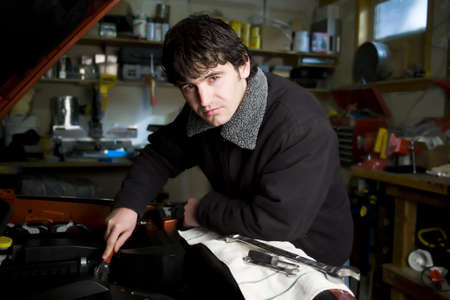 A mechanic in his workshop working on a vehicle engine photo