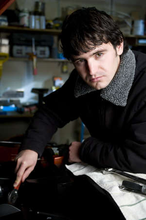Portrait of a young male mechanic working on a vehicle in his shop photo