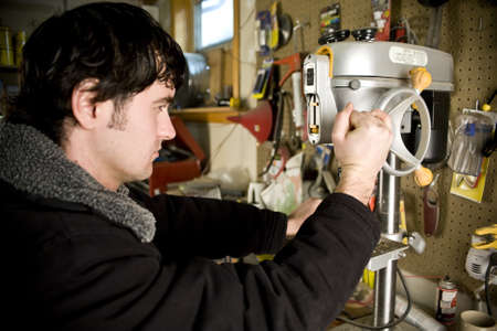 Man working in workshop using a drill press photo