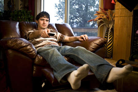 A man watching tv holding remote control towards tv Stock Photo - 4335534