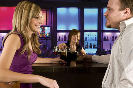 A couple sitting at bar with bar tender pouring a drink photo