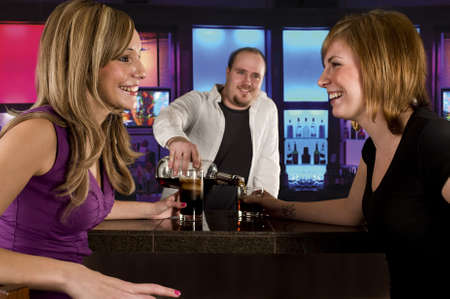 two young women at the bar having drinks photo