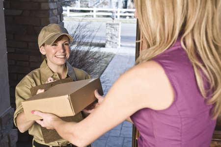 delivery driver: Courier or delivery driver delivering package to a woman at home Stock Photo