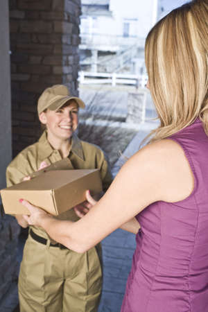 Delivery driver or courier handing package over to a woman photo