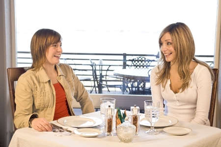 2 friends sitting at a table eating lunch and laughing Stock Photo