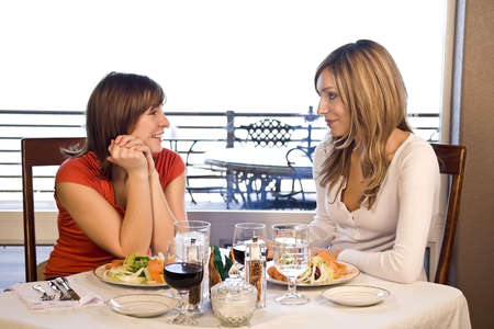 2 friends having lunch at a cafe laughing and smiling photo