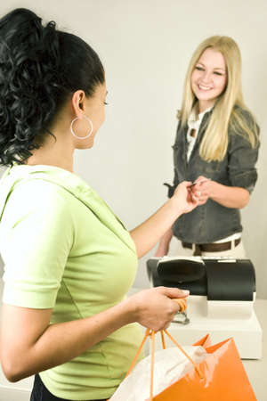 A woman at the register giving back a customers credit card Stock Photo - 5352988