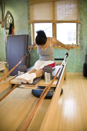 Young hispanic woman doing pilates in a gym photo