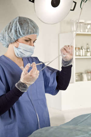 Nurse injecting with syringe into iv tube in a hospital photo