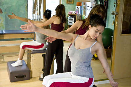 Young hispanic woman and trainer doing pilates in a gym