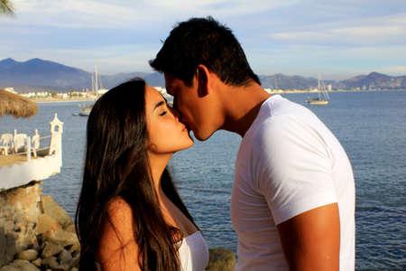 novios besandose: Joven pareja bes�ndose mutuamente en frente del Oc�ano Foto de archivo