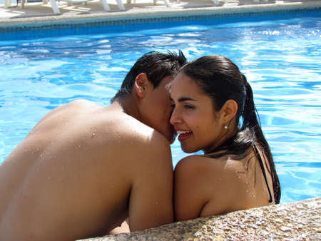 A couple enjpying time together in the pool kissing photo