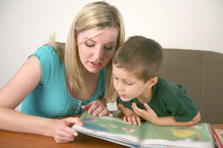 A young child reads a book with help from a teacher or tutor  Stock Photo