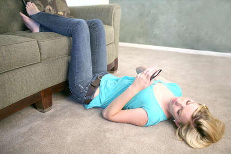 A young woman laying on the floor looking at her cell phone texting photo