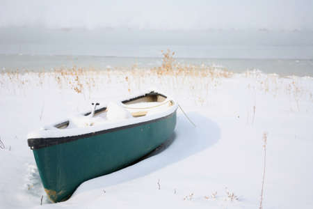 canoe on the shore of a lake during winter covered in snow photo