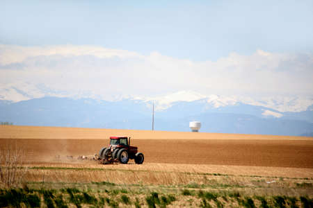 tractor plowing fields on a large farm with mouuntains and snow in the background Banco de Imagens