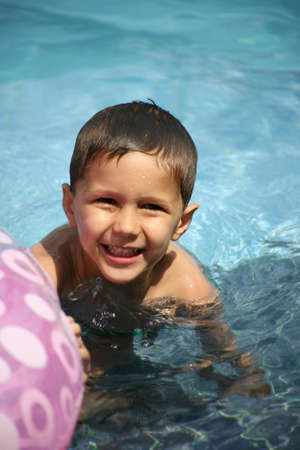float tube: Young boy playing in a pool with a float tube