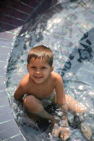 young boy sitting in a pool smiling looking up photo