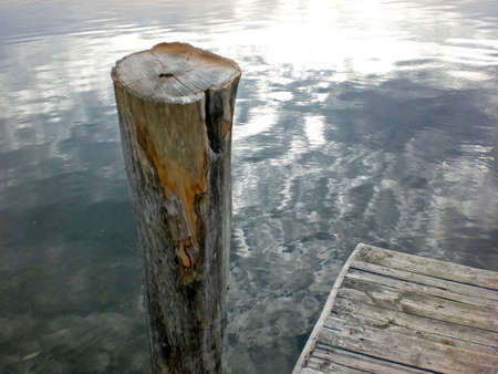 post: Gray waters with dock post Stock Photo