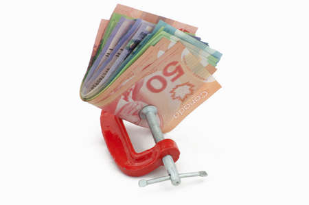 canadian cash: Canadian money in a clamp.