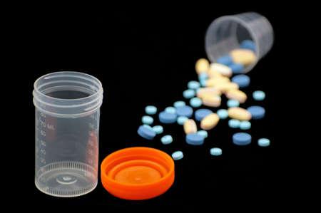 Urine sample bottle and pills. Imagens