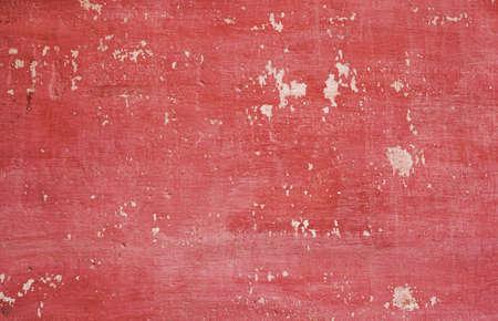 Textura sucia de la pared vieja fuera de color. Pared de yeso de color rojo rosa, desgastada y agrietada. Foto de archivo