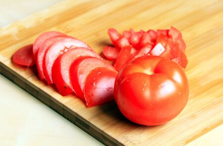 Cut fresh tomato on the chopping board Stock Photo