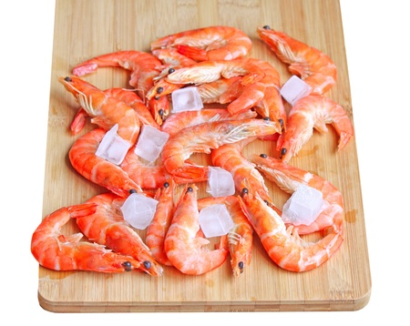 Fresh red shrimps with ice on the chopping board - isolated
