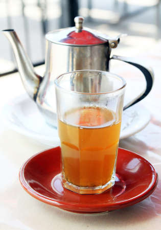 A glass of mint tea and kettle behind