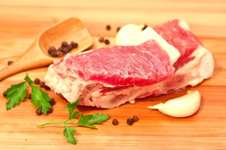 Raw beef with spices and vegetables on the cutting board photo