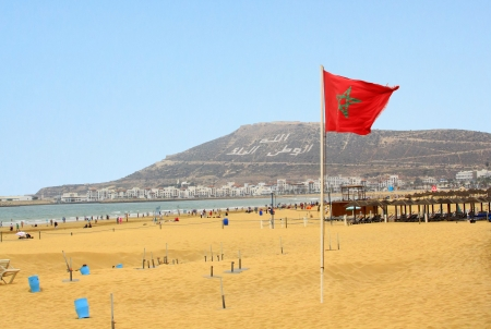 The beautiful beach in Agadir with flag of Morocco
