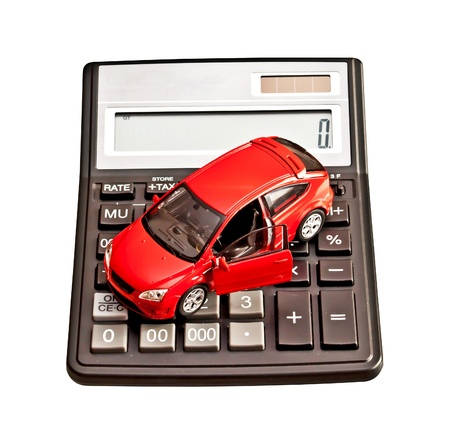 Toy car and calculator over white. Concept for buying, renting, insurance, fuel, service and repair costs photo