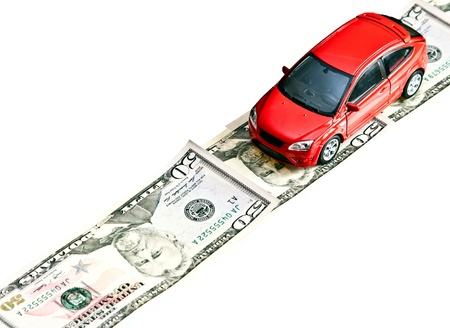 Red toy car on the money road, isolated on white photo