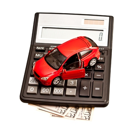 Toy car and calculator over white. Concept for buying, renting,  fuel, service and repair costs photo