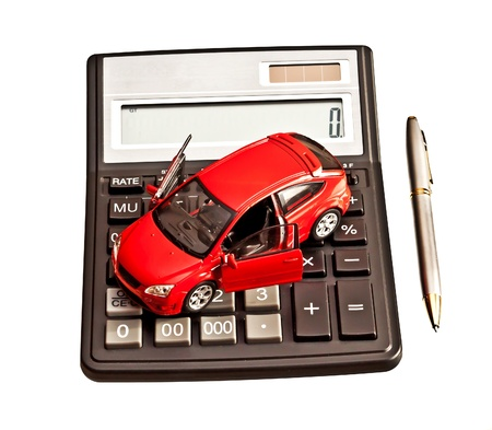 Toy car and calculator over white  Rent, buy, repair or insurance car concept photo