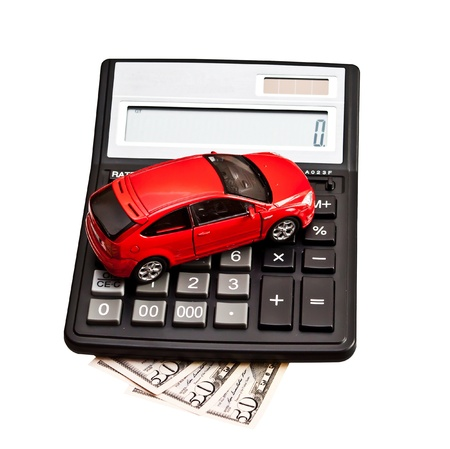 Toy car and calculator over white  Concept for buying, renting, insurance, fuel, service and repair costs Stock Photo